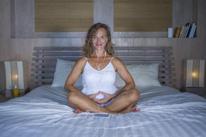 Schönes und geeignetes gesundes übendes Yoga der Frau 30s im Bett konzentrierte sich in der Meditationsübung, die Herzform mit ih lizenzfreie stockfotos