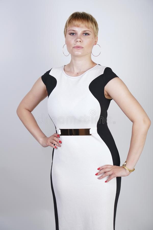 Schönes und großes blondes Mädchen mit kurzen Haaren in einem modischen Bürokleid auf einem weißen Hintergrund im Studio Stiljuge lizenzfreie stockbilder