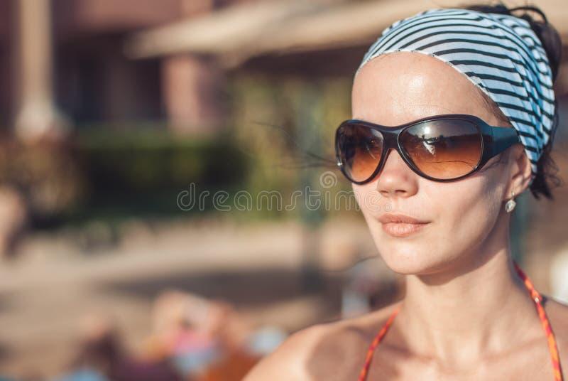 Schönes und junges Mädchen in einem gestreiften orange Badeanzug und in den Sonnenbrilleständen und Sonnenbräunen gegen den unsch stockfotografie