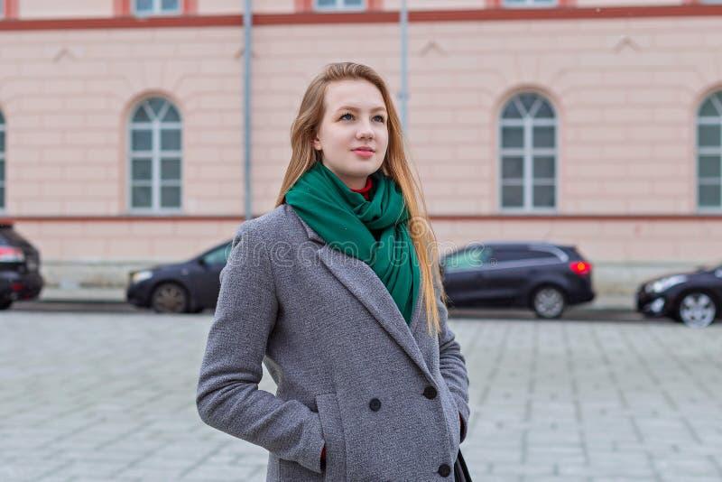 Schönes und junges Mädchen in einem Mantel geht auf die tägliche Stadt stockbild