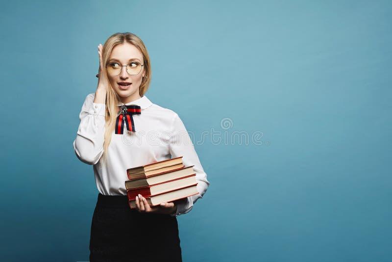 Schönes und modernes überraschtes blondes vorbildliches Mädchen im Eyewear, in der stilvollen Bluse und im schwarzen Spitzerock,  stockbild