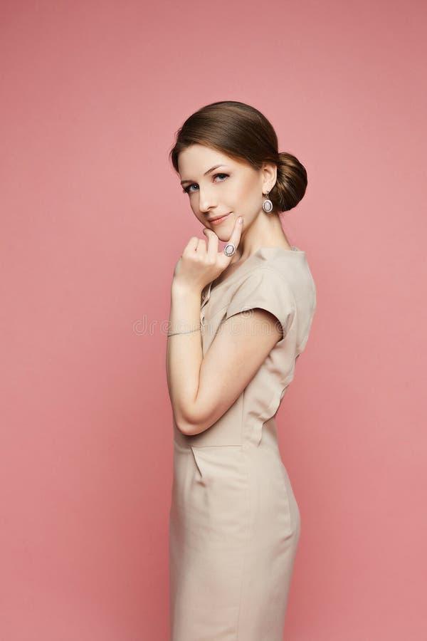 Schönes und modernes brunette vorbildliches Mädchen in einem beige Kleid mit dem stilvollen Schmuck lokalisiert am rosa Hintergru lizenzfreie stockfotografie