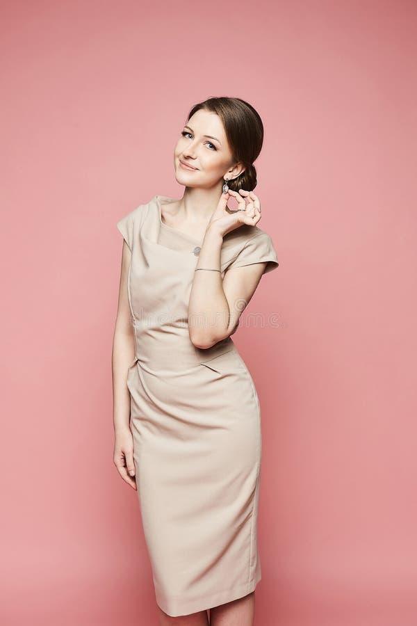 Schönes und modernes brunette vorbildliches Mädchen mit blauen Augen und mit hellem Make-up im modischen beige Kleid, das sie jus stockbild