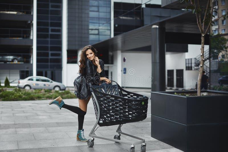 Schönes und modernes Brunettemodellmädchen, in der Lederjacke, in kurzen Hosen und in Strümpfen, draußen aufwerfend lizenzfreie stockfotos