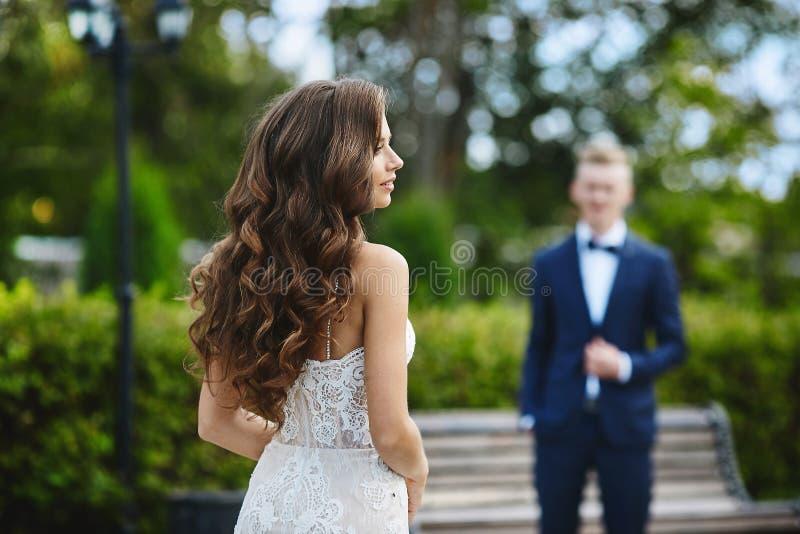 Schönes und modernes Brunettemodellmädchen mit sexy Körper und mit Hochzeitsfrisur im stilvollen weißen Spitzekleid gehend zu ihr stockfotografie