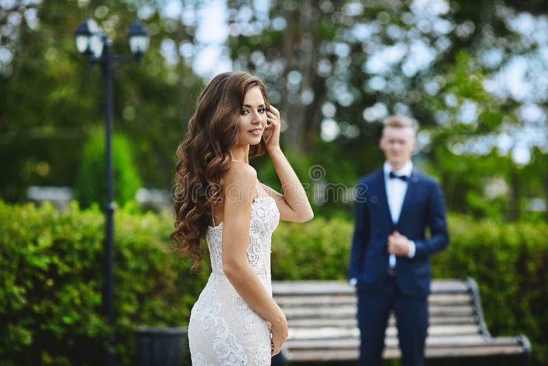Schönes und modernes Brunettemodellmädchen mit sexy Körper im stilvollen weißen Spitzekleid, das Kamera betrachtet und zu ihrem b stockfotografie
