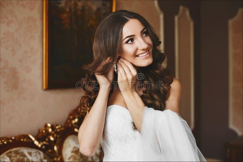Schönes und modernes Brunettemodellmädchen mit stilvoller Hochzeitsfrisur, im weißen Kleid der Spitzes setzt an ihren Ohrring stockfoto