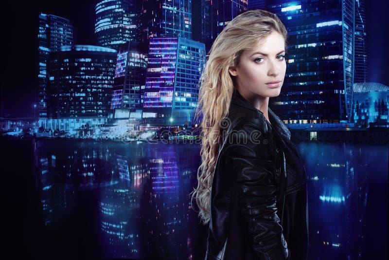 Schönes und stilvolles junges blondes Mädchen, auf dem Hintergrund der Nachtstadt stockfotos