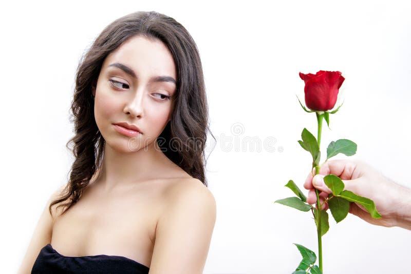 Schönes verärgertes Mädchen empfängt eine Rotrose Sie ist überrascht und betrachtet die Blumen und Anfangsdas lächeln lizenzfreies stockbild