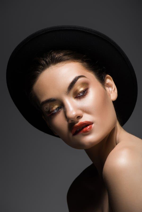 schönes verlockendes Mädchen in der schwarzen schneidenden Lippe des geglaubten Hutes stockfotos