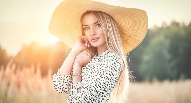 Schönes vorbildliches Mädchen, das auf einem Feld, Naturfreien im breiten geströmten Strohhut genießend aufwirft blonde junge Fra lizenzfreie stockfotografie
