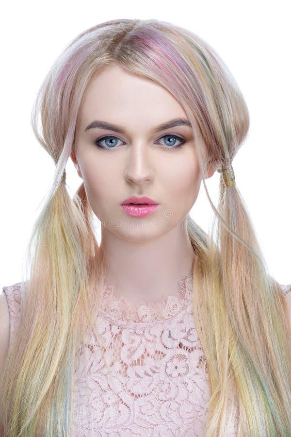 Schönes vorbildliches Mädchen mit dem blonden Haar mit farbiger Haarnahaufnahme auf einem weißen Hintergrund leckt Süßigkeit gest stockfotografie