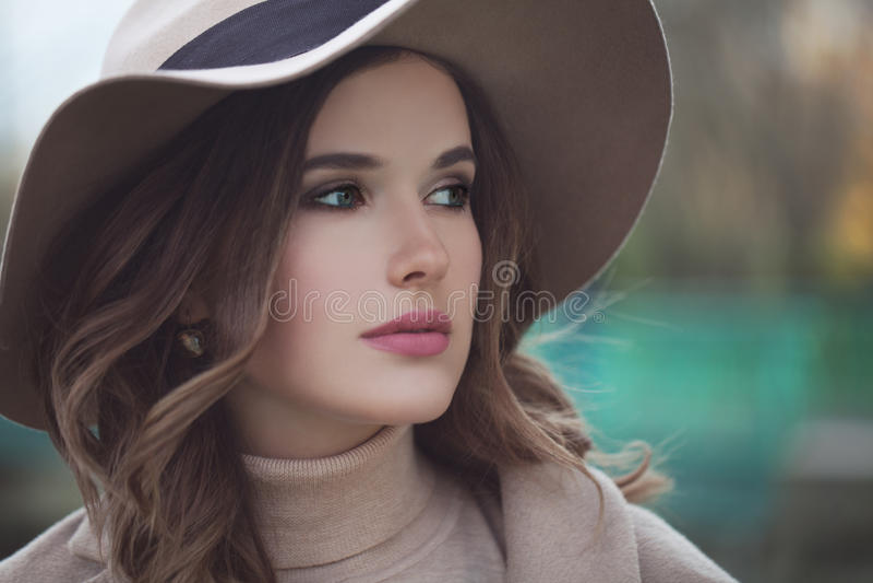 Schönes vorbildliches Woman im beige Hut draußen stockbild