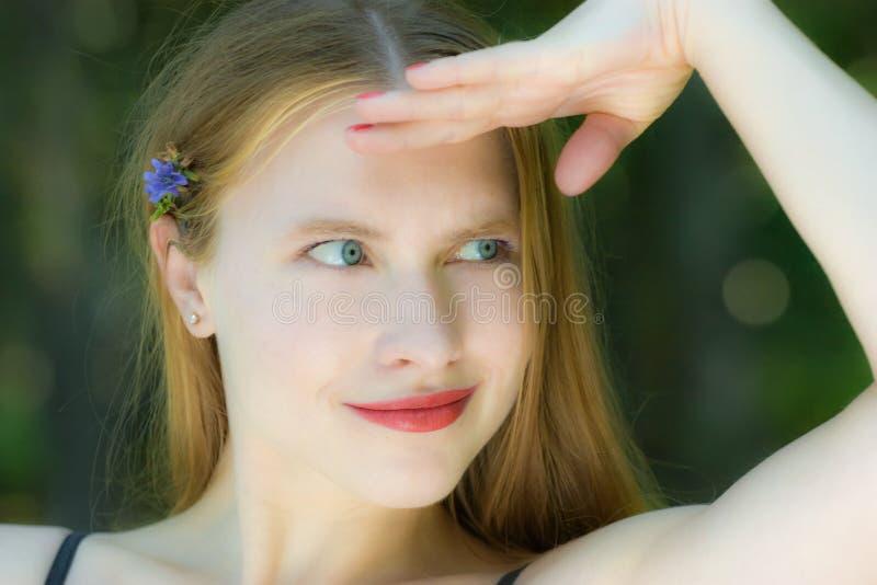 Schönes waman mit einer kleinen blauen Blume stockbilder