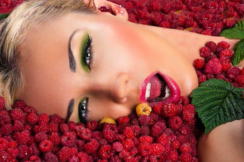 Schönes weibliches Gesicht in den Himbeeren lizenzfreie stockfotografie