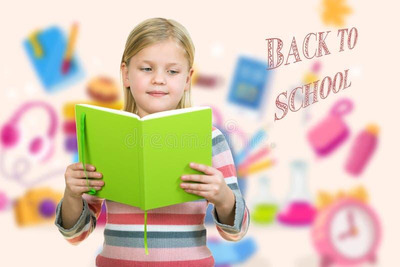 Schönes weibliches Kind mit dem netten blonden Haar und blauen den Augen, die Notizbuch halten lizenzfreie stockfotos