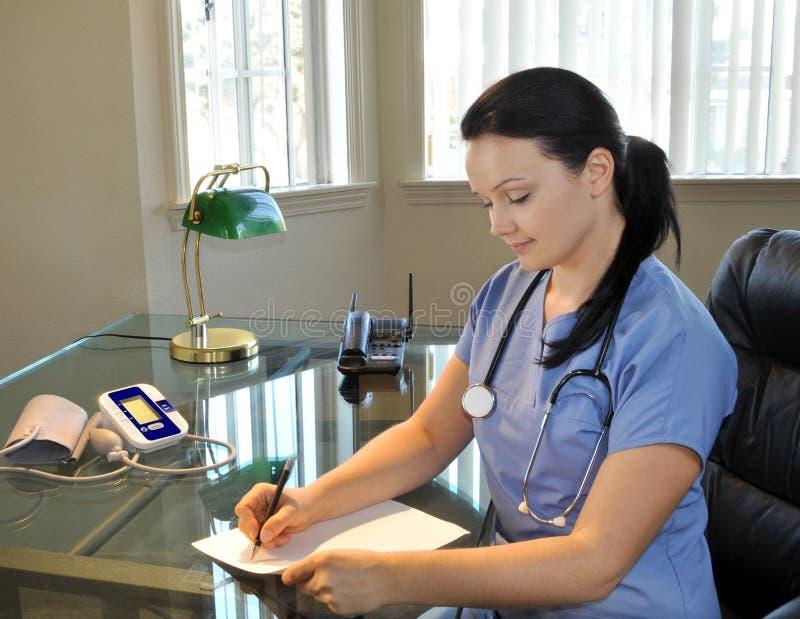 Schönes weibliches Krankenschwesterschreiben stockbild