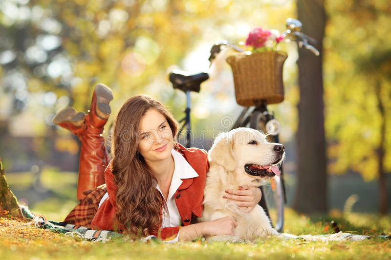 Schönes weibliches Lügen auf einem grünen Gras mit Hund in einem Park stockbilder