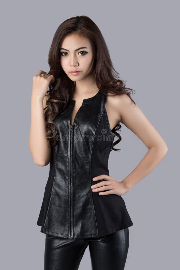 Schönes weibliches Modell, das ein ledernes Kleid trägt lizenzfreie stockbilder