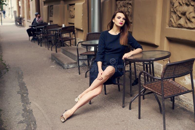 Schönes weibliches Modell, das am Straßencafé sitzt stockbilder