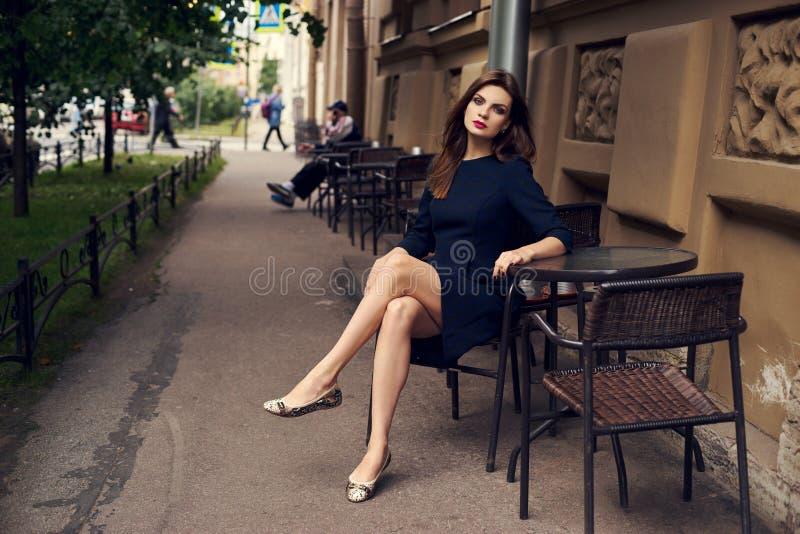 Schönes weibliches Modell, das am Straßencafé sitzt stockfoto