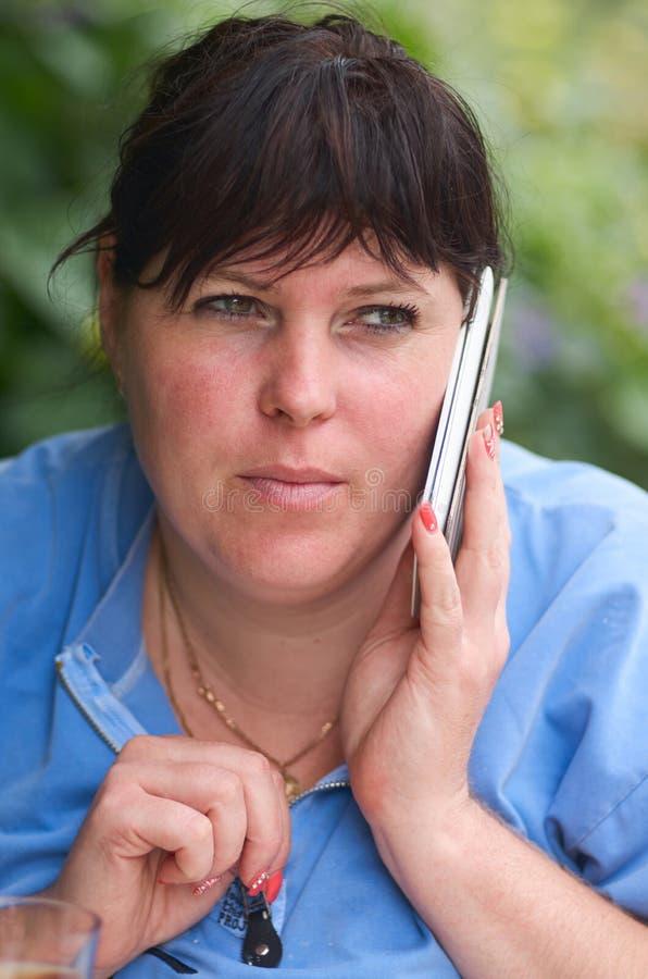 Schönes weibliches Sprechen am Handy Mädchen mit der Telefonherstellung lizenzfreie stockfotos