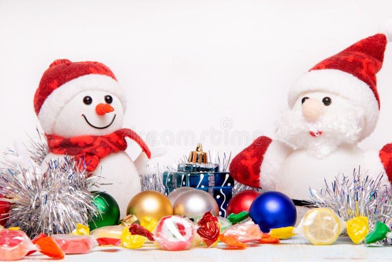 Schönes Weihnachts- und des neuen Jahreszusammensetzung mit Santa Claus und Schneemann in den roten Hüten und in den Schals in de lizenzfreie stockbilder