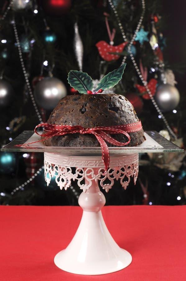 Schönes Weihnachtsgedeck vor dem Weihnachtsbaum, einen klassischen Pflaumenpudding kennzeichnend lizenzfreies stockbild