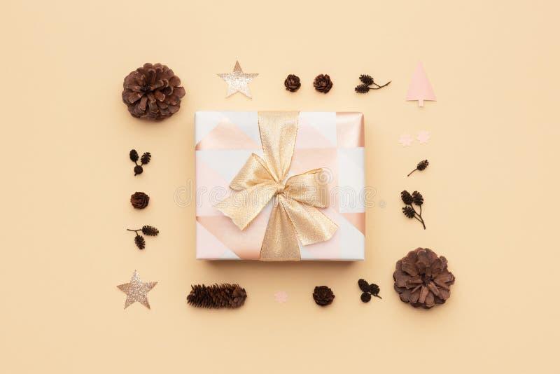 Schönes Weihnachtsgeschenk verziert mit einem Bandbogen lokalisiert auf beige Hintergrund Rosa und Gold eingewickelter Weihnachts lizenzfreie stockfotos
