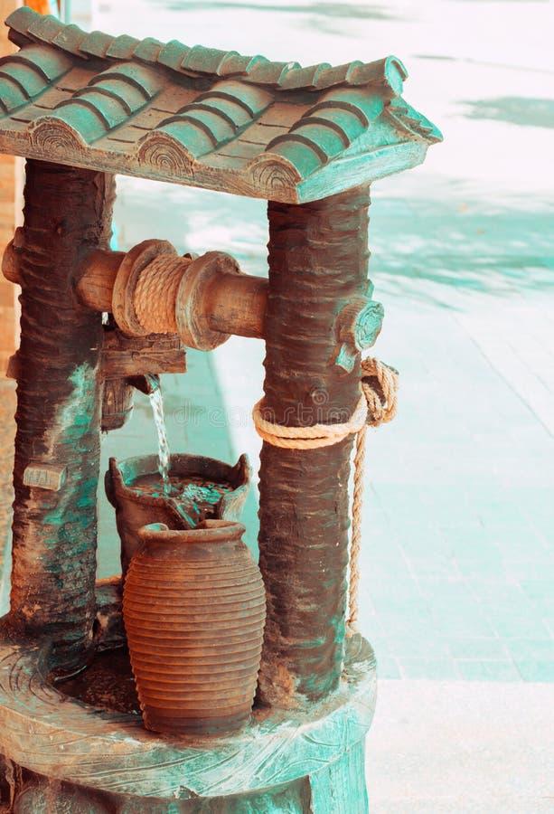Schönes Weinlesewasser strömender feng shui Brunnen mit dekorativen Elementen des Krugseils in der asiatischen Art Getont im oran stockbilder
