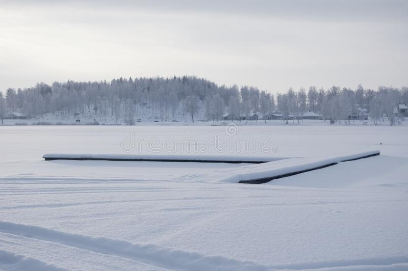 Schönes Winterbesonderefoto Gefrorener See an der Winterzeit Foto mit schönem Wald im Hintergrund und ein Dock, das in liegt stockfoto