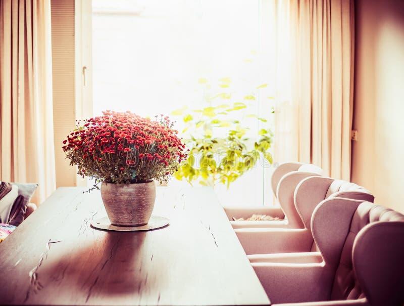 Schönes Wohnzimmer mit Chrysanthemen blüht Bündel auf Abendtische am Fensterhintergrund stockfotografie