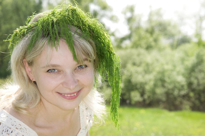 Schönes youg Mädchen, das Blumenwreathnahaufnahme trägt stockbild