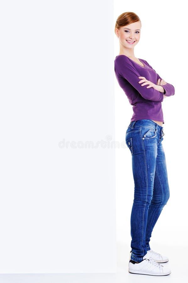 Schönes youn Mädchen nahe unbelegter Anschlagtafel stockbild