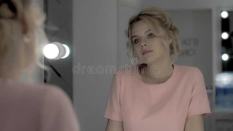 Schönes zartes Mädchen im rosa Kleid, das den Spiegel im Make-upraum betrachtet lizenzfreies stockfoto