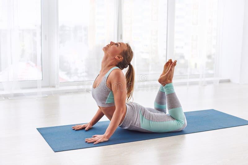 Schönheit übt Yoga asana Raja Bhujangasana - Königskobrahaltung am Yogastudio stockfotografie