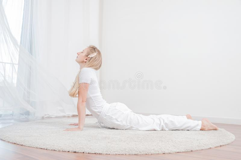 Schönheit übt Yoga zu Hause und tut Kobraübung, Bhujangasana-Haltung lizenzfreies stockbild