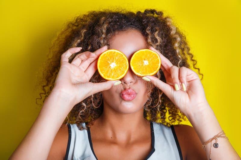 Schönheit afroes-amerikanisch vorbildliches Girl nimmt saftige Orangen stockfoto