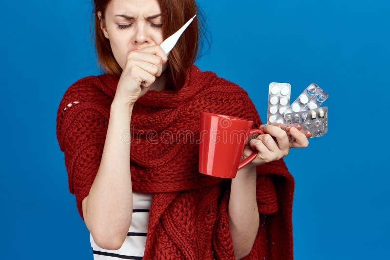 Schönheit auf einem blauen Hintergrund hält einen Becher, Pillen, Thermometer, Krankheit, Kranker, Grippe lizenzfreie stockbilder