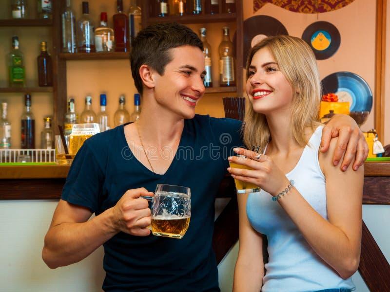 Schönheit Blondine und Brunette bemannen das Lächeln und das Trinken in der Bar lizenzfreies stockbild