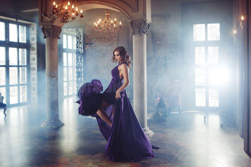Schönheit Brunette-Modellfrau, wenn purpurrotes Kleid geglättet wird Luxusmake-up und Frisur der schönen Mode stockfoto