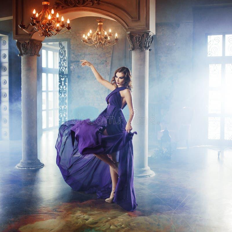 Schönheit Brunette-Modellfrau, wenn purpurrotes Kleid geglättet wird Luxusmake-up und Frisur der schönen Mode stockfotografie