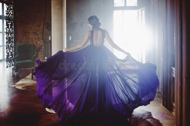 Schönheit Brunette-Modellfrau, wenn purpurrotes Kleid geglättet wird Luxusmake-up und Frisur der schönen Mode lizenzfreies stockbild