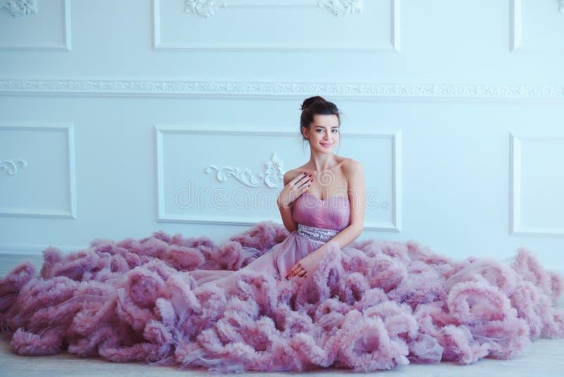 Schönheit Brunette-Modellfrau, wenn purpurrotes Kleid geglättet wird Luxusmake-up und Frisur der schönen Mode Verlockendes Mädche stockfotos
