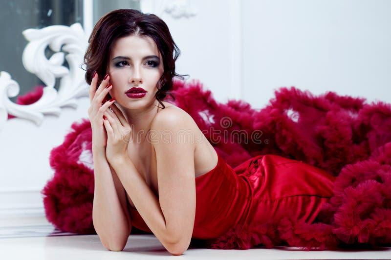 Schönheit Brunette-Modellfrau, wenn rotes Kleid geglättet wird Luxusmake-up und Frisur der schönen Mode lizenzfreie stockbilder