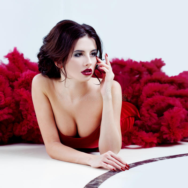 Schönheit Brunette-Modellfrau, wenn rotes Kleid geglättet wird Luxusmake-up und Frisur der schönen Mode lizenzfreies stockfoto
