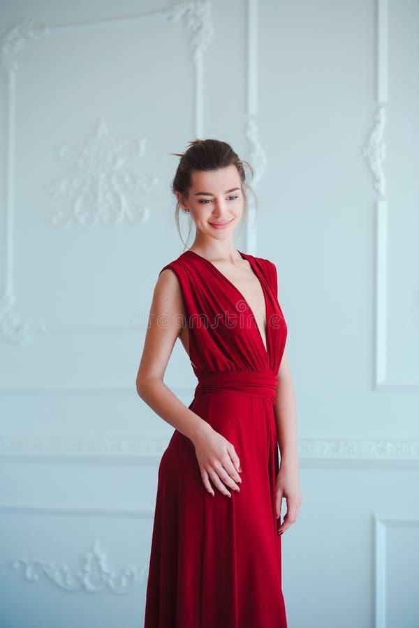 Schönheit Brunette-Modellfrau, wenn rotes Kleid geglättet wird Luxusmake-up und Frisur der schönen Mode Verlockendes Mädchen stockbild