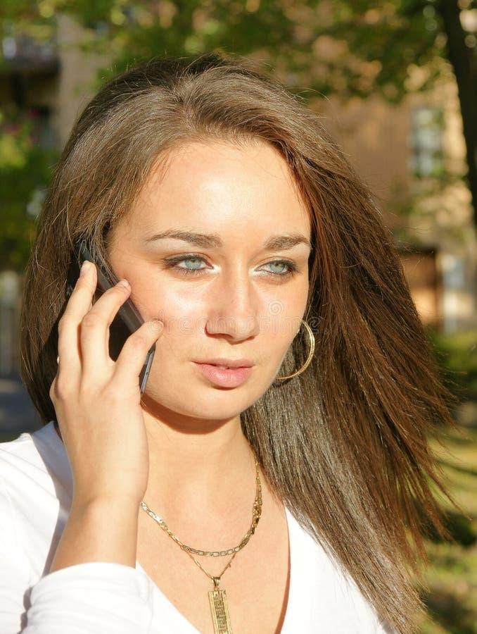 Schönheit Brunettefrau am Handy lizenzfreies stockbild