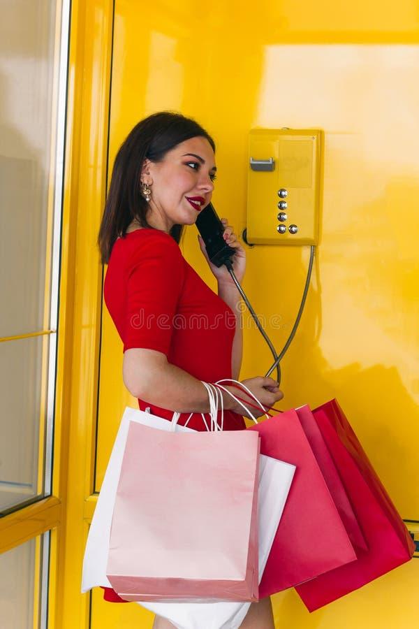 Schönheit in den roten Kleideraufträgen ein Taxi in einer Retro- Telefonzelle im Mall nach dem Einkauf stockfotos