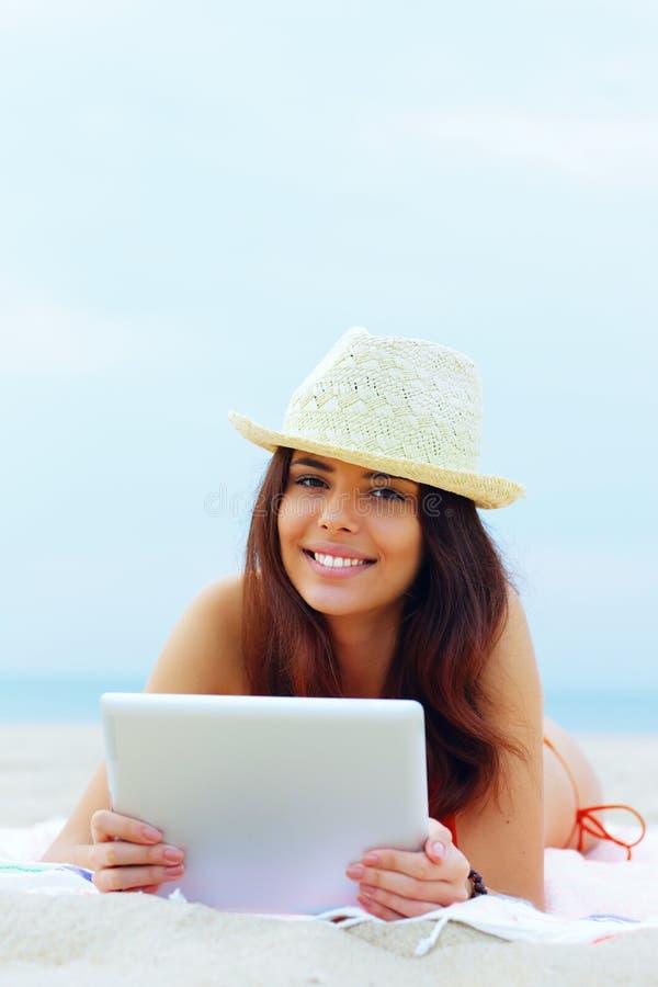 Schönheit in der Schwimmenklage unter Verwendung ihrer Tablette auf dem Strand stockbild